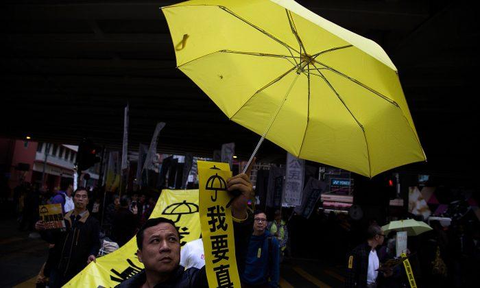 Мужчина держит желтый зонтик во время марша десятков тысяч протестующих за реальное всеобщее избирательное право 1 февраля 2015 года в Гонконге. (Лам Ик Фей / Getty Images)   Epoch Times Россия