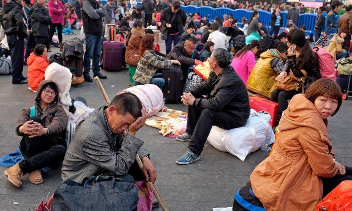 Путешественники ждут своих поездов, проезжая мимо железнодорожного вокзала Гуанчжоу 28 января 2014 года в Гуанчжоу, Китай. (Теодор Кэй / Getty Images) | Epoch Times Россия