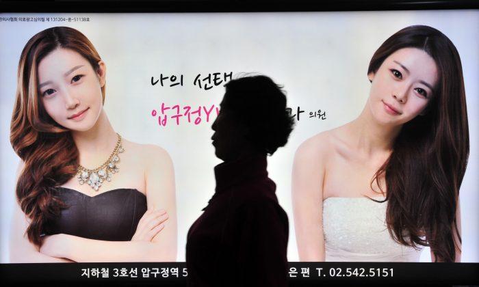 Пешеход проходит мимо рекламы клиники пластической хирургии на станции метро в Сеуле 26 марта 2014 г. (Jung Yeon-Je / AFP / Getty Images) | Epoch Times Россия