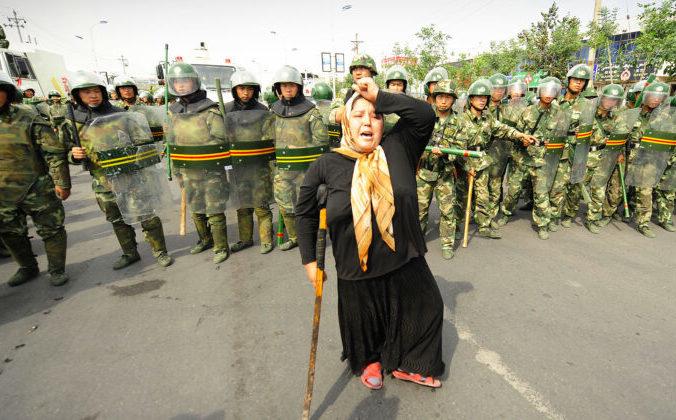 Китайские омоновцы наблюдают за протестом пожилой уйгурской женщины в Урумчи, в китайской провинции Синьцзян.  PETER PARKS/ Getty Images | Epoch Times Россия