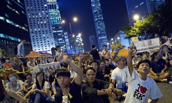 Протестующие, выступающие за демократию, недоуменно смотрят в прямом эфире, транслируя переговоры между правительственными чиновниками Гонконга и студентами на оккупированной митингующими территории у здания правительства в районе Адмиралтейства Гонконга, вторник, 21 октября 2014 г. (AP Photo / Винсент Ю) | Epoch Times Россия