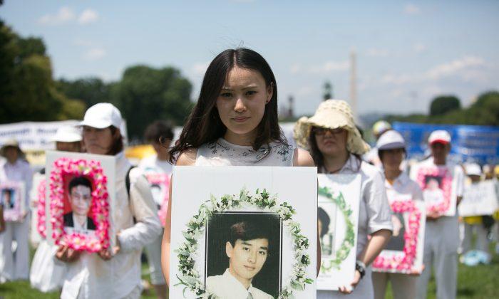 Молодая женщина держит плакат во время митинга в Вашингтоне 17 июля 2014 года с изображением китайца, замученного до смерти за то, что он практиковал Фалуньгун в Китае. (Эдвард Дай / Великая Эпоха) | Epoch Times Россия