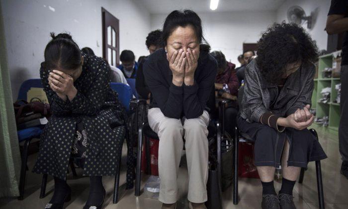 Китайские христиане молятся во время службы в подпольной независимой протестантской церкви 12 октября в Пекине, Китай. Китай, официально атеистическая страна, накладывает ряд ограничений на христиан и разрешает юридическое исповедание веры только в одобренных государством церквях. (Кевин Фрайер / Getty Images) | Epoch Times Россия