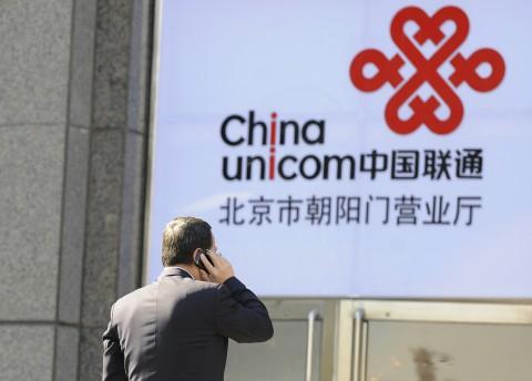 Офисный работник разговаривает по мобильному телефону на фоне логотипа China Unicom, партнёра Apple в Китае, 5 января 2012 года, Пекин. За коррупцию уже арестовано два руководителя компании. Фото: Liu Jin/AFP/Getty Images | Epoch Times Россия