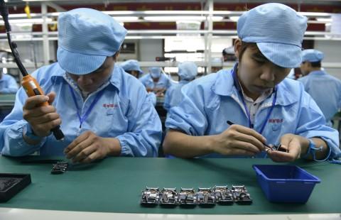 Китайские рабочие собирают часы — дешёвую местную альтернативу часам Apple Watch 22 апреля 2015 года, Шэньчжэнь, Китай. Фото: STR/AFP/Getty Images | Epoch Times Россия