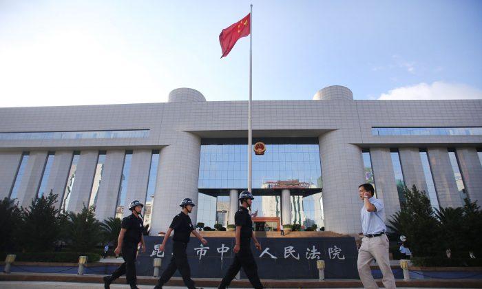 Полицейский патруль у ворот суда промежуточной инстанции Куньмина в Куньмине, провинция Юньнань на юго-западе Китая, 12 сентября 2014 г. (STR / AFP / Getty Images)   Epoch Times Россия