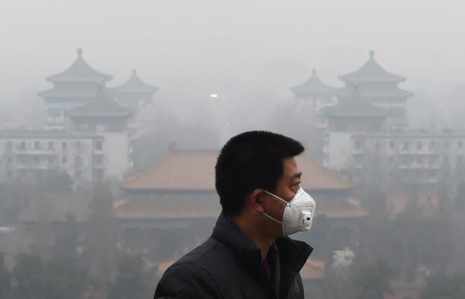 Жители Пекина одевают маски, чтобы защитить себя от вредного воздуха. Фото: GREG BAKER/AFP/Getty Images | Epoch Times Россия