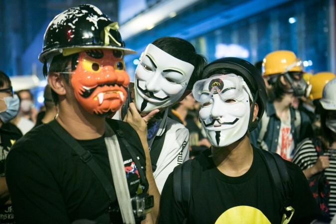 Протестующие в масках Гая Фокса стоят на передовой линии во время противостояния с полицией в Монгкоке, Гонконг, 5 ноября 2014 года. Фото: Benjamin Chasteen/Epoch Times   Epoch Times Россия