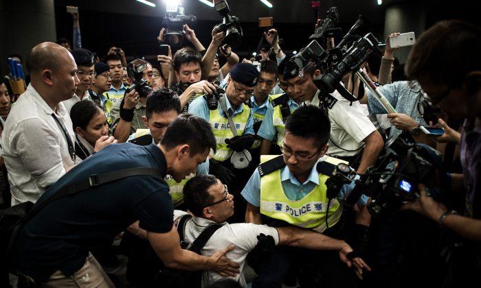 ОМОН удаляет протестующих с территории Законодательного совета в Гонконге, 14 июня 2014 г. Протестующие возражают против плана правительства по превращению сельскохозяйственных угодий в жилые комплексы. (Филипп Лопес / AFP / Getty Images)   Epoch Times Россия