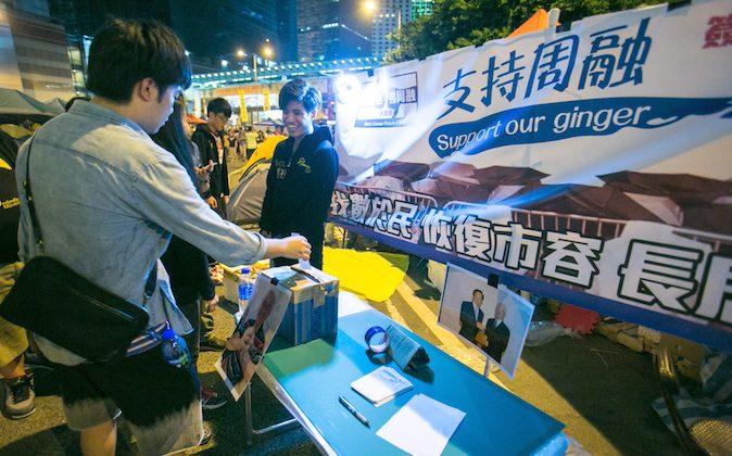 Люди выражают свою поддержку в имитационной будке в Центральном округе, оформленной так, чтобы она выглядела как будка для борьбы с оккупацией, которая была в районе Гонконга 3 ноября 2014 г. (Бенджамин Честин / Epoch Times) | Epoch Times Россия