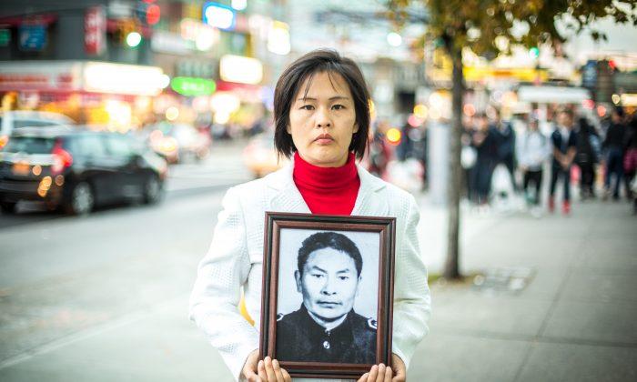 Цзян Ли из Флашинга, Квинс, 1 ноября 2015 года, держит фотографию своего отца, убитого коммунистической партией Китая в Китае за то, что он практиковал Фалуньгун. (Бенджамин Честин / Великая Эпоха) | Epoch Times Россия