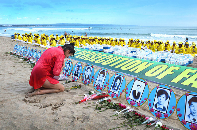 Люди возлагают цветы к портретам сторонников Фалуньгун, погибших в Китае в результате репрессий. Город Легиан, остров Бали. Июль 2014 года. Фото: minghui.org   Epoch Times Россия
