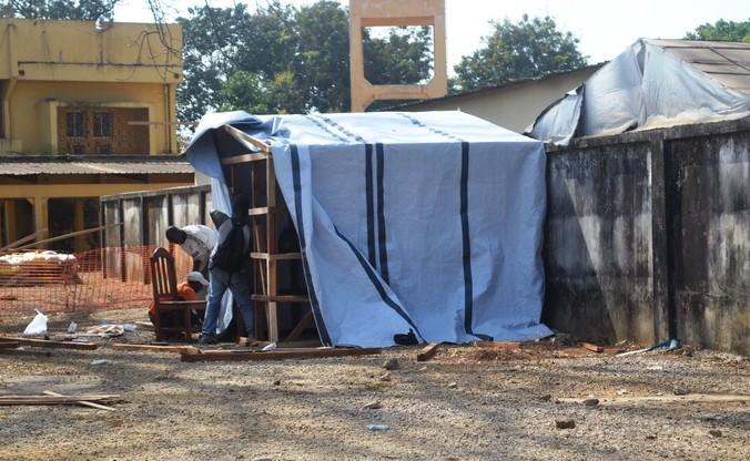 Рабочие сооружают палатку в изолированной зоне, где есть пациенты с подозрением на лихорадку Эбола. Несколько случаев  заболевания смертельно опасной лихорадкой Эбола зафиксированы в столице Гвинеи Конакри 29 марта 2014 года. Фото: CELLOU BINANI/AFP/Getty Images | Epoch Times Россия