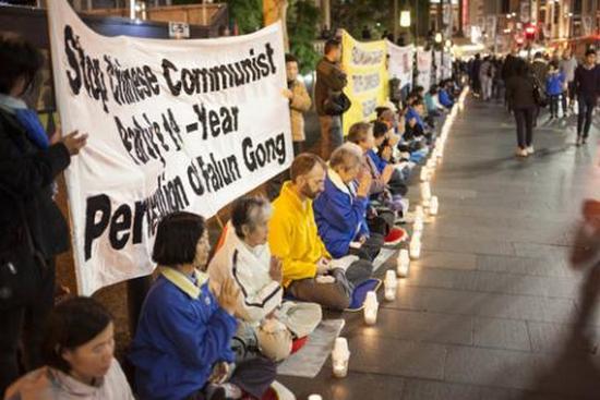 Последователи Фалуньгун проводят акцию со свечами, призывая общественность помочь остановить преследование их единомышленников в Китае. Сидней (Австралия). 2013 год. Фото: news.zhengjian   Epoch Times Россия