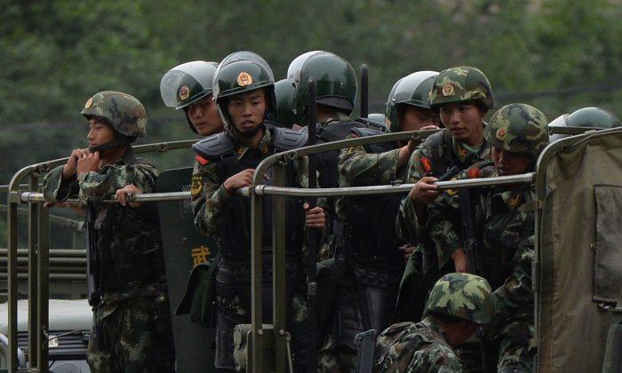 Китайская военизированная полиция готовится к поездке на грузовиках во время церемонии «демонстрации силы» в Урумчи 29 июня 2013 года. Китайский режим пересматривает законы, чтобы предотвратить утечку военной информации. (МАРК РАЛСТОН / AFP / Getty Images)   Epoch Times Россия