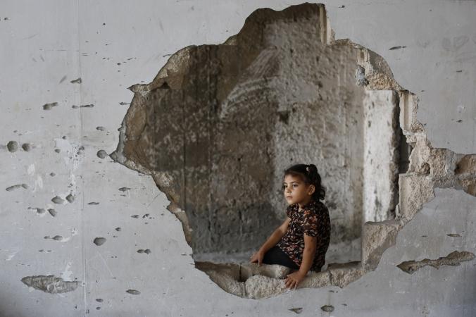 11 октября: палестинская девочка из семьи Мсабех сидит в комнате её дома, который был разрушен в течение 50-дневной войны между израильской армией и боевиками из ХАМАС в городе Газа, Израиль. Семье некуда идти и они продолжают жить в развалинах. Фото:  MOHAMMED ABED/AFP/Getty Images | Epoch Times Россия