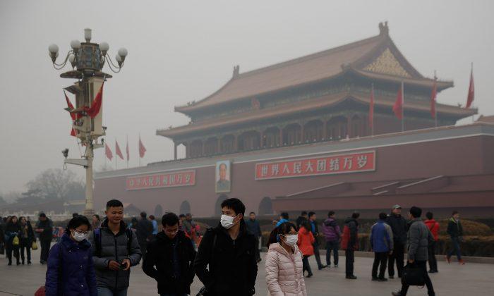 Китайские туристы в масках на площади Тяньаньмэнь во время сильного загрязнения 25 февраля 2014 года в Пекине, Китай. (Линтао Чжан / Getty Images) | Epoch Times Россия