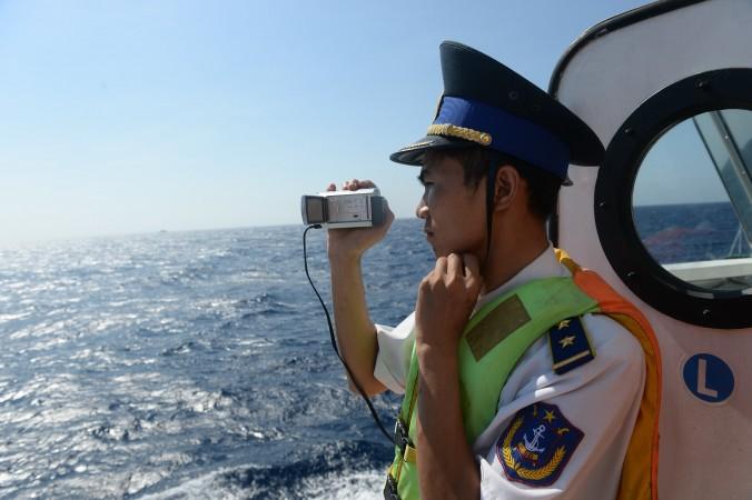 Офицер вьетнамской береговой охраны снимает на видео китайские корабли вблизи установки китайской буровой платформы в спорных водах Южно-Китайского моря. Фото: Hoang Dinh Nam/AFP/Getty Images | Epoch Times Россия
