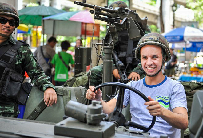Иностранный турист в каске сидит в военной машине армии Таиланда в Бангкоке после объявления военного положения 20 мая 2014 года. В стране обострился политический кризис, который в течение 6 месяцев унёс жизни не менее 28 человек. Фото: Rufus Cox/Getty Images | Epoch Times Россия