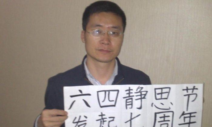 Бывший китайский адвокат по правам человека Тан Цзинлин в начале 2014 года держит плакат в поддержку протестующих, убитых на площади Тяньаньмэнь во время резни 1989 года (AP). | Epoch Times Россия