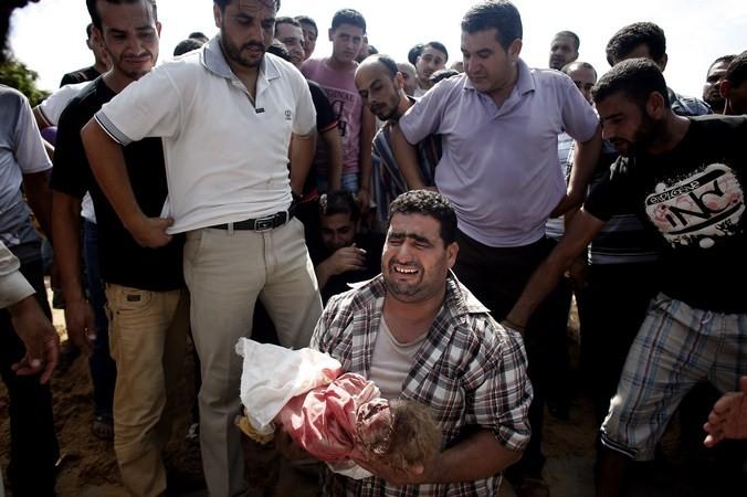 Палестинец оплакивает ребёнка, одного из восьми членов его семьи, убитых за одну ночь во время израильского обстрела, Сектор Газа, 19 июля, 2014 год. Фото:  THOMAS COEX / AFP / Getty Images | Epoch Times Россия