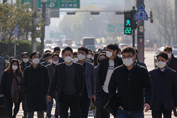 Пешеходы в масках переходят улицу в Сеуле 26 ноября 2020 года. ED JONES/AFP via Getty Images | Epoch Times Россия
