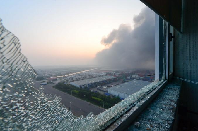Из разбитого окна квартиры виден дым на месте взрывов в Тяньцзине, Китай, 13 августа 2015 года. Фото: STR/AFP/Getty Images   Epoch Times Россия