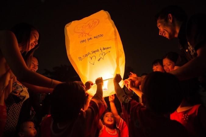 Родители и дети запускают в небо фонари с молитвами в память о пассажирах исчезнувшего «Боинга-777», Куала-Лумпур, Малайзия, 13 сентября 2014 г. Фото: MOHD RASFAN/AFP/Getty Images   Epoch Times Россия