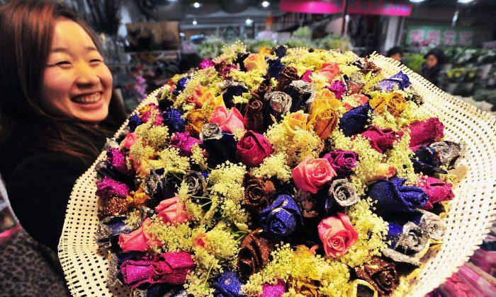 Женщина позирует с букетом роз на цветочном рынке в Китае в преддверии Дня святого Валентина. (ChinaFotoPress / Getty Images) | Epoch Times Россия