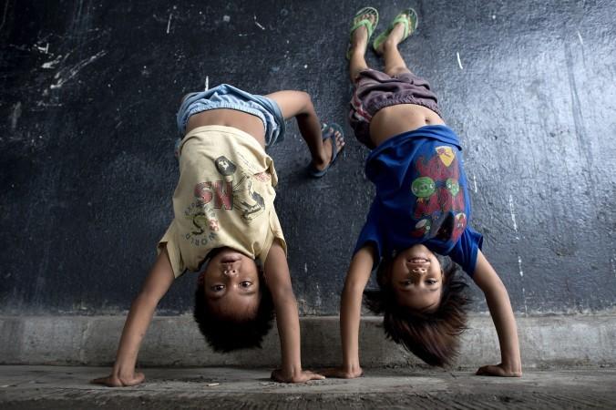 31 августа: дети показывают свои акробатические навыки в подземном переходе в районе, где недавно были снесены дома нелегальных поселенцев в Маниле, Филиппины, 28 августа 2014 года. Фото: Noel Celis/AFP/Getty Images | Epoch Times Россия