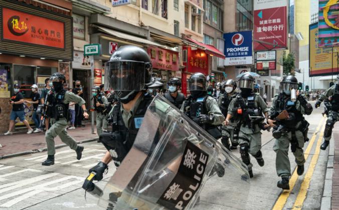 Спецназ бежит по улице навстречу пешеходам во время операции по сдерживанию толпы на демонстрации в Гонконге 1 июля 2020 года. Anthony Kwan/Getty Images   Epoch Times Россия