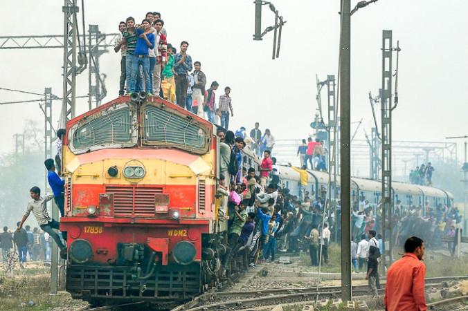 Индийские пассажиры стоят и висят на поезде, когда он отходит от станции на окраине Нью-Дели. Фото: MONEY SHARMA/AFP/Getty Images | Epoch Times Россия
