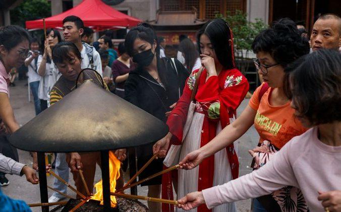 Китайцы поджигают ароматические палочки во время фестиваля середины осени в храме Цзинань в Шанхае, 4 октября 2017 года. Фото: Chandan Khanna/AFP/Getty Images | Epoch Times Россия