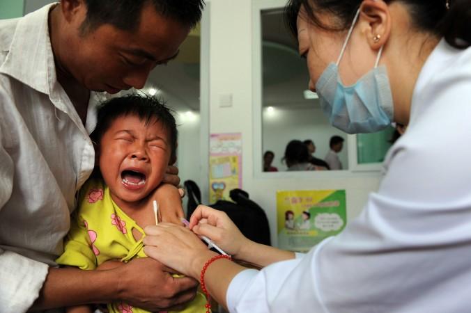 Китайскому ребёнку делают прививку от кори в провинции Аньхуэй 11 сентября 2010 г. Милиция раскрыла нелегальную сеть по торговле вакциной в провинции Шаньдун. Фото: STR/AFP/Getty Images | Epoch Times Россия