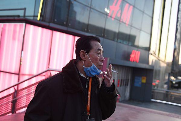 Мужчина опускает маску, чтобы выкурить сигарету, Пекин, 17 февраля 2020 года. GREG BAKER/AFP via Getty Images | Epoch Times Россия