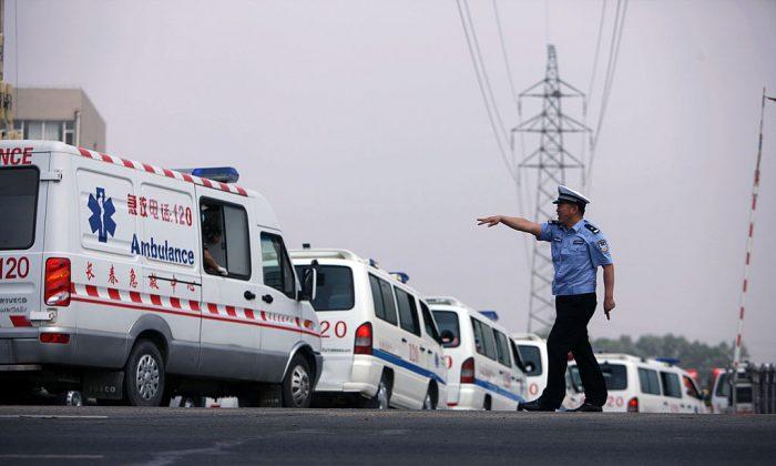Полицейский останавливает машину скорой помощи в Дэхуэй, китайская провинция Цзилинь, 3 июня 2013 года. Неофициальные операторы машин скорой помощи стали большой проблемой в Китае. (STR / AFP / Getty Images)   Epoch Times Россия