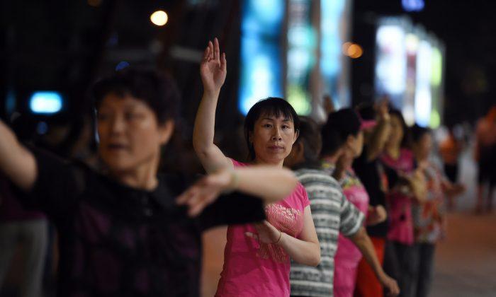 Группа женщин танцует перед торговым центром возле жилого комплекса в Пекине, 7 сентября 2015 г. (GREG BAKER / AFP / Getty Images) | Epoch Times Россия