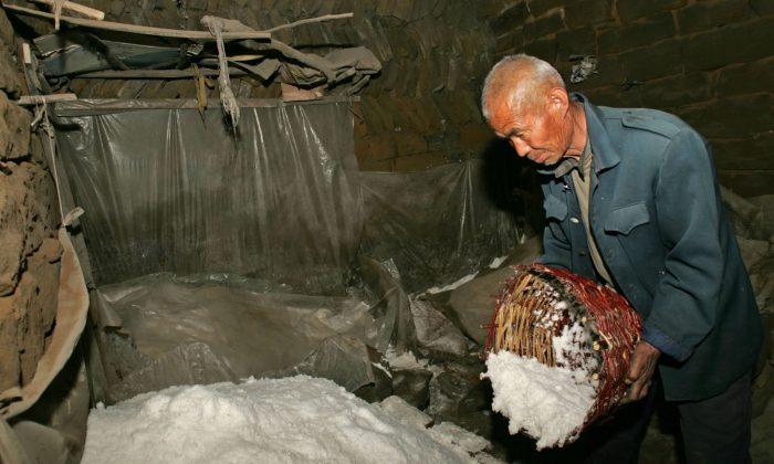 Китайский фермер насыпает соль в кучу соли в деревне Лицзява в уезде Цзычжоу, провинция Шэньси, Китай, 31 марта 2006 г. (China Photos / Getty Images) | Epoch Times Россия
