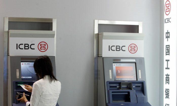 Посетитель опробует один из новейших банкоматов на банковской выставке в Пекине 13 сентября 2007 г. (STR / AFP / Getty Images) | Epoch Times Россия