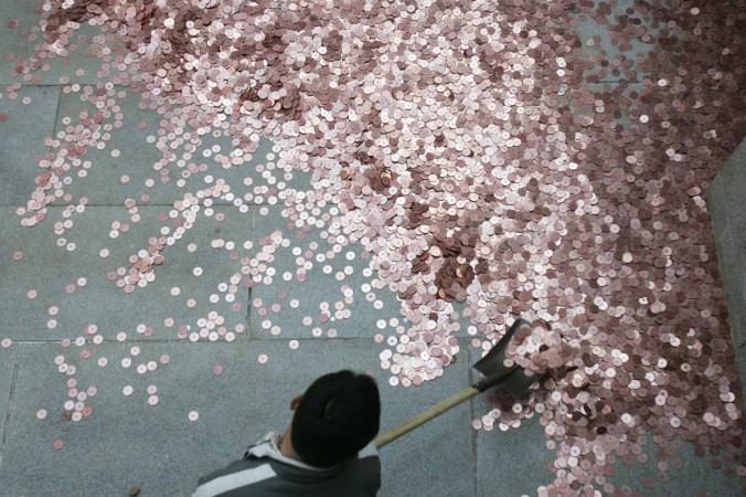 Рабочий собирает монетки, брошенные туристами в пруд на удачу, в Храме белых облаков в Пекине, 18 февраля 2007 г. Китайские валютные резервы исчезают так же быстро, как эти монетки. Фото: China Photos/Getty Images | Epoch Times Россия