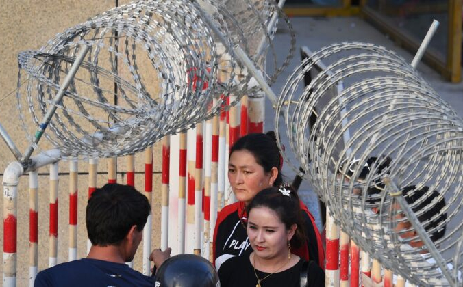 Уйгурка (в центре) проходит через вход на базар в Хотане, на северо-западе Китая, в районе Синьцзян, 31 мая 2019 г.  GREG BAKER/AFP via Getty Images)   Epoch Times Россия