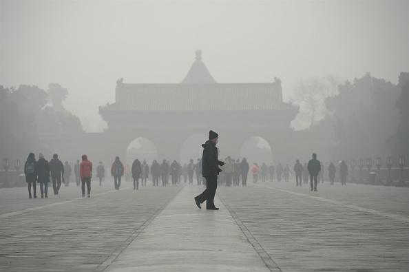 Пожилой мужчина идет перед группой людей во время сильного смога. 20 декабря 2016 год, Пекин. Фото / Wang Zhao/AFP/Getty Images | Epoch Times Россия
