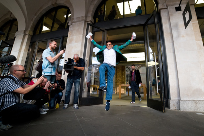 20 сентября: первый покупатель iPhone 6 в Ковент-Гарденс (Англия) прыгает от радости 19 сентября, после того как ему пришлось простоять в очереди несколько дней. Всего за новинкой выстроилось более тысячи человек. Фото: Ben A. Pruchnie/Getty Images | Epoch Times Россия