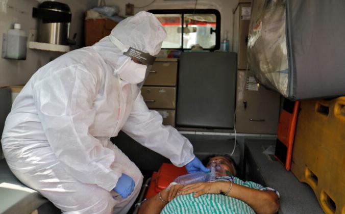 Анкита Патель, 31 год, фельдшер в машине скорой помощи держит кислородную маску женщине с COVID-19. Больную доставляют в больницу Ахмедабада, Индия, на лечение. 29 апреля 2021 г. (Amit Dave / Reuters) | Epoch Times Россия