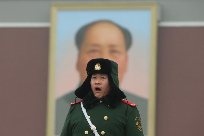 Полицейский стоит на страже перед гигантским портретом покойного председателя Мао Цзэдуна на площади Тяньаньмэнь в 2013 году в Пекине, Китай. (Фэн Ли / Getty Images) | Epoch Times Россия