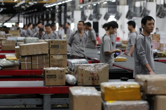 Работники распределяют посылки в городе Шэньчжэнь, Китай, 11 ноября, 2013 г. Частные компании в Китае прекратили инвестирование в дальнейшее расширение. Фото: ChinaFotoPress via Getty Images | Epoch Times Россия