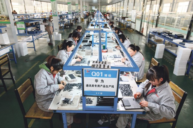 Рабочие в цехе электронной компании в Тэнчжоу, в восточной китайской провинции Шаньдун, 1 февраля 2016 г. Фото: STR/AFP/Getty Images | Epoch Times Россия