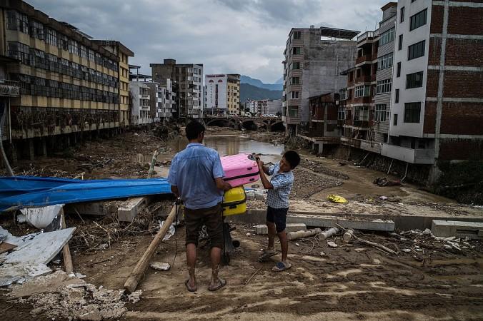 Люди покидают дома в пострадавшем от тайфуна городе Баньдон в провинции Фуцзянь, Китай, 12 июля 2016 года. Фото: Lam Yik Fei/Getty Images | Epoch Times Россия
