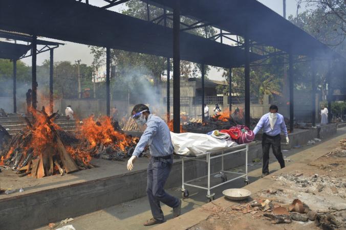Родственники несут тело умершего от COVID-19, в то время как в крематории Нью-Дели, Индии, сжигают трупы других многочисленных жертв вируса, 1 мая 2021 года. (Amit Sharma/AP Photo) | Epoch Times Россия