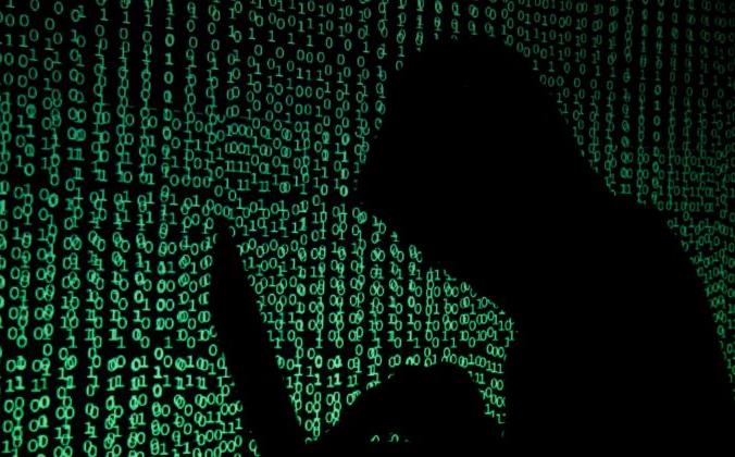 Мужчина в капюшоне держит портативный компьютер на фоне кибер-кода. Иллюстрация сделана 13 мая 2017 г. (Kacper Pempel/Illustration/Reuters)   Epoch Times Россия